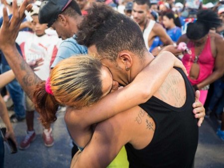 couple of cubans kissing in a parade in honour to the revolution