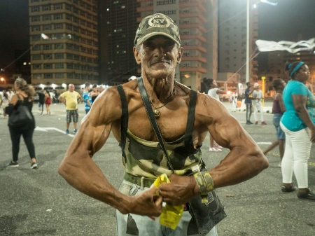 muscle man posing for a picture in havana´s carnival, cuban photography