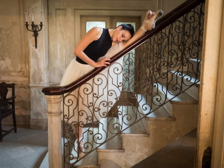 ballet dancer stretching her muscles on a colonial stairway in cuba