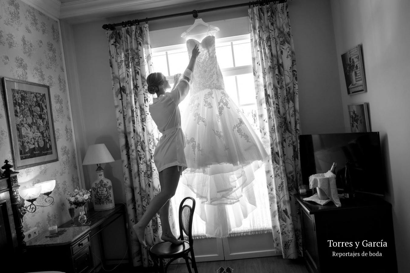 descolgando su vestido - Fotografías - Libros y reportajes de boda diferentes.