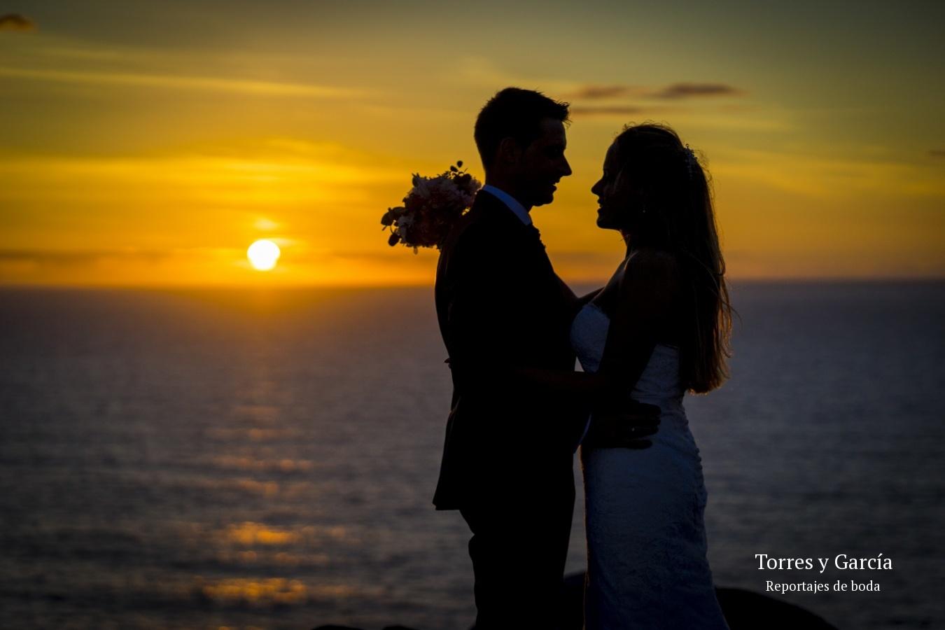 Silueta de los novios con la puesta de sol sobre el mar - Fotografías - Libros y reportajes de boda diferentes.