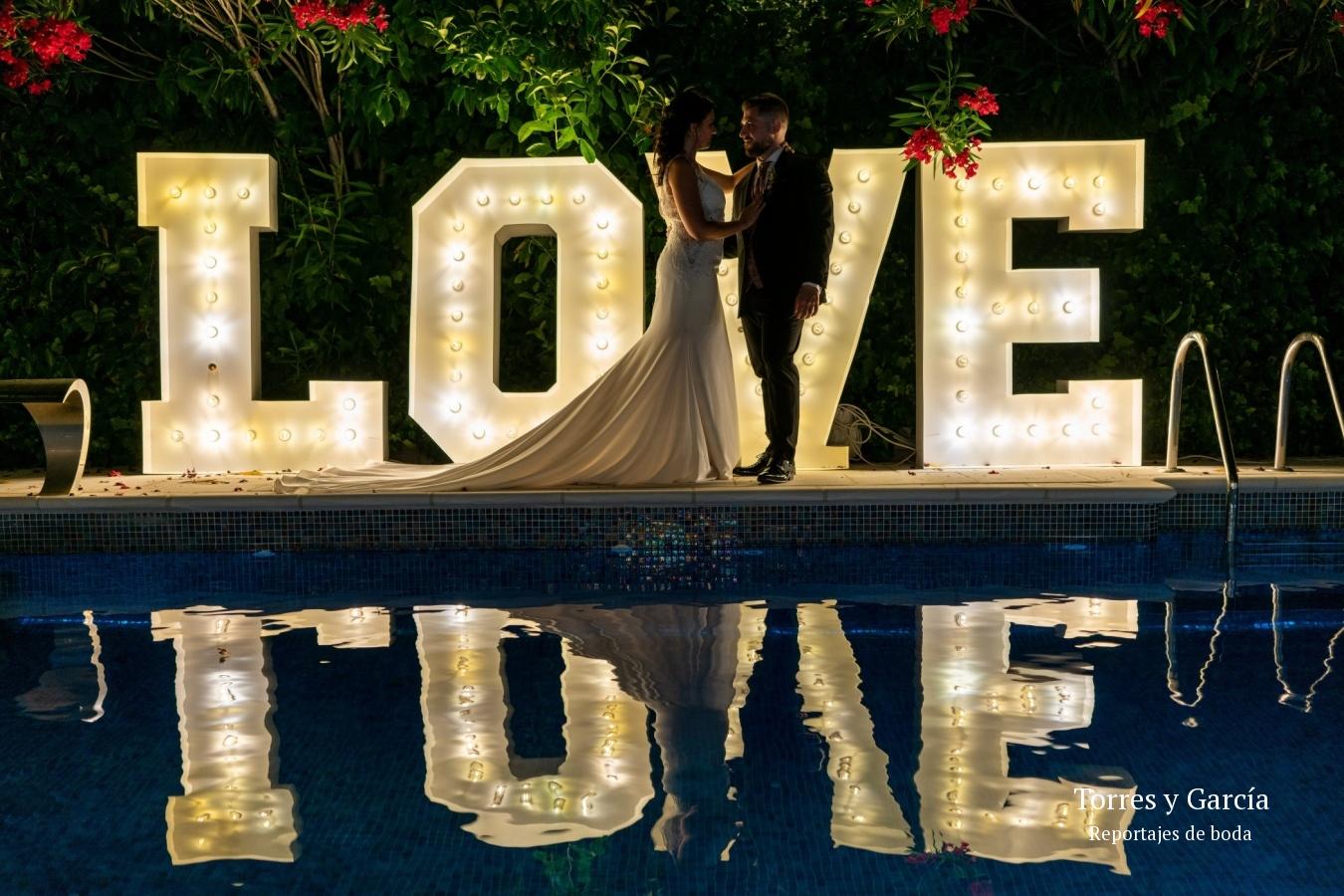 reflejo del letrero love en el jardín del palacete - Fotografías - Libros y reportajes de boda diferentes.
